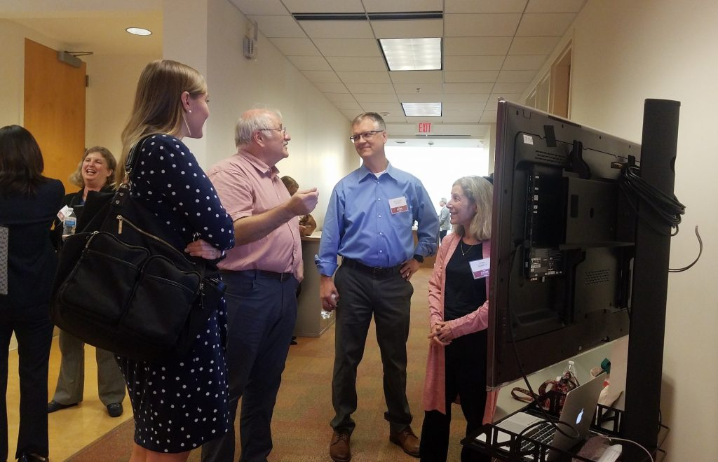 A group of researchers discuss their work during the poster session portion of the STEM summit.