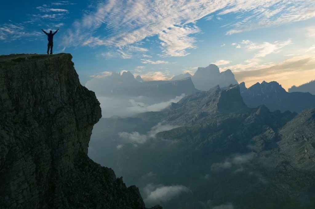 A person standing at the top of a cliff overlooking other mountain peaks.